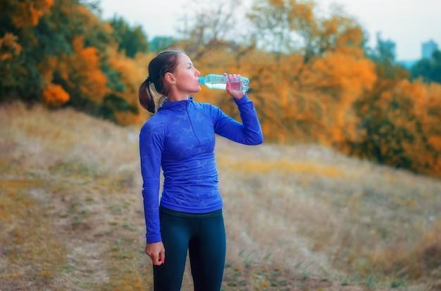 Uma mulher magra, caucasiana, praticante de corrida, com uma jaqueta esportiva azul, capuz e perneiras pretas, bebe água da garrafa depois de correr