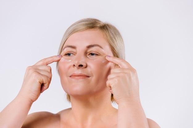 Uma mulher mais velha aplica um creme revitalizante sob os olhos com os dedos indicadores. foto ampliada