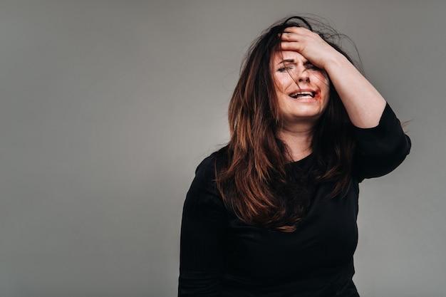 Uma mulher maltratada com roupas pretas segura a cabeça contra uma superfície cinza isolada. violência contra a mulher.