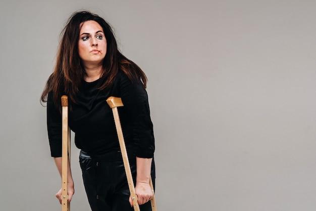 Uma mulher maltratada em roupas pretas com rodízios nas mãos sobre um fundo cinza.