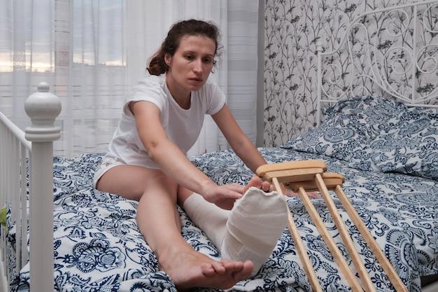 Uma mulher massageia os dedos de uma perna quebrada com as mãos