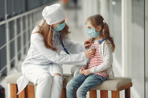 Uma mulher médico está examinando uma criança com estetoscópio