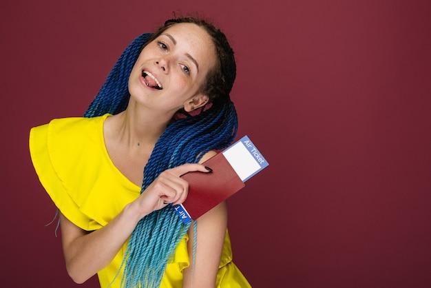 Uma mulher moderna e elegante, sorridente, com um vestido amarelo, passagens aéreas e passaporte