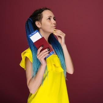 Uma mulher moderna e elegante, sorridente, com um vestido amarelo, passagens aéreas e um passaporte na mão