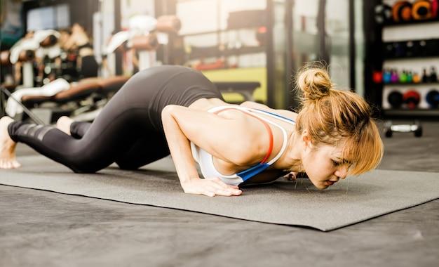 Uma mulher morena asiática exercitando-se fazendo ioga no ginásio de fitness.