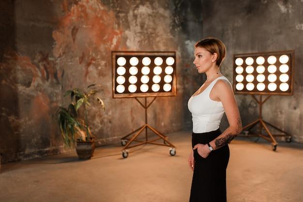 Uma mulher morena atraente em uma sala de design de interiores loft com carrinho de luz de lâmpada retrô