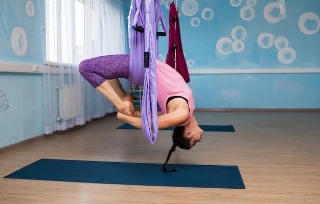 Uma mulher morena com roupas esportivas praticando ioga em uma rede no estúdio