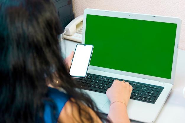 Uma mulher morena de costas para a câmera faz compras na internet pagando com um cartão bancário online na tela verde. foto horizontal