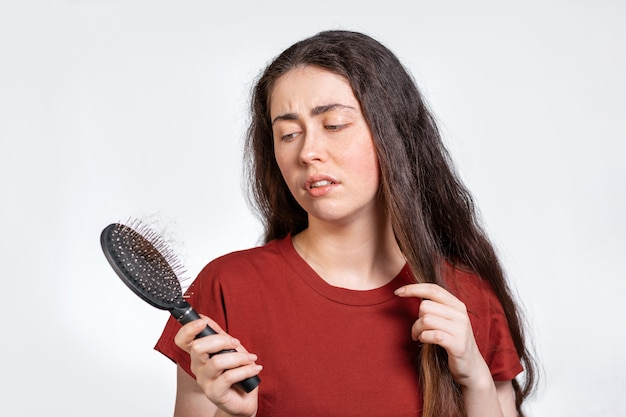 Uma mulher morena descontente segura um pente com uma mecha de cabelo rasgado e olha para o cabelo
