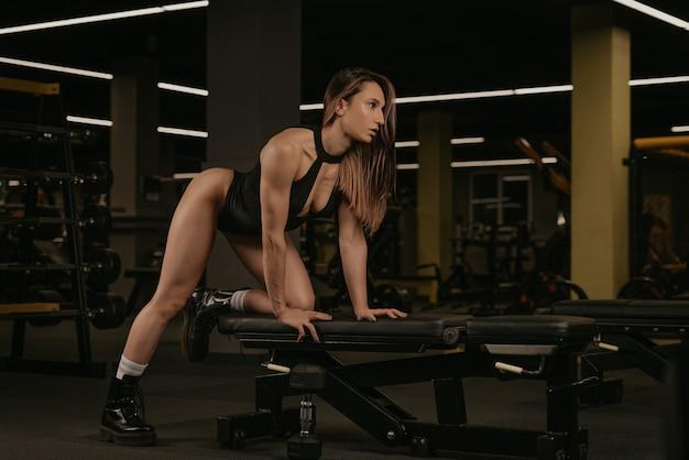 Uma mulher morena em forma está relaxando depois de uma remada com halteres de um braço com o joelho no banco. uma garota musculosa usa um corpete preto e botas durante um treino nas costas em uma academia.