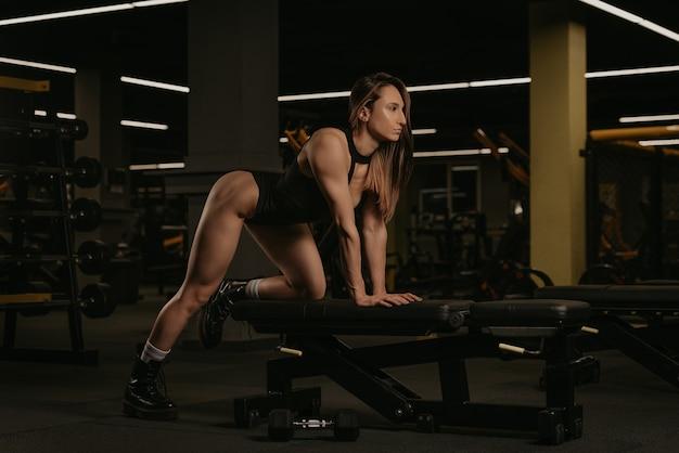 Uma mulher morena em forma está se alongando após uma remada com halteres de um braço e o joelho no banco. uma garota musculosa usa um corpete preto e botas durante um treino nas costas em uma academia.