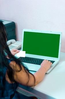 Uma mulher morena em seu escritório doméstico faz compras na internet pagando com uma tela verde online de cartão de crédito. foto vertical