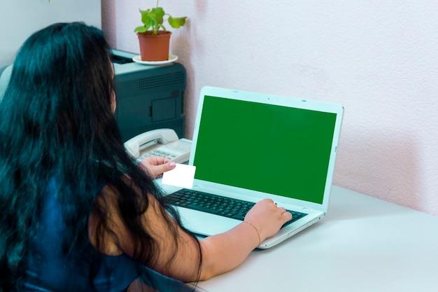 Uma mulher morena em um escritório doméstico faz compras na internet pagando com uma tela verde com um cartão do banco. foto horizontal