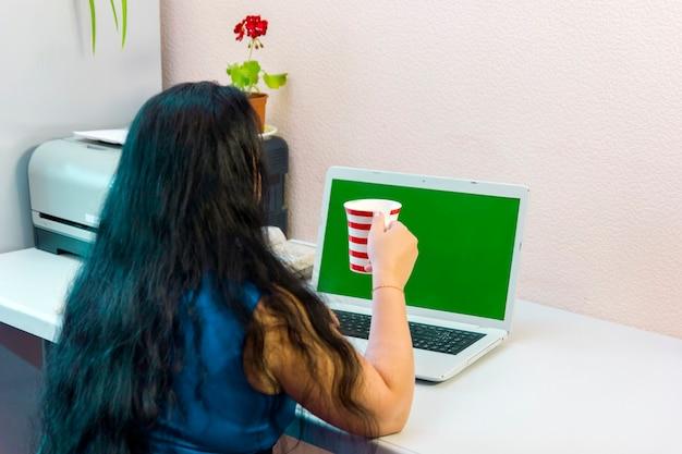 Uma mulher morena em um escritório em casa trabalha para um laptop e bebe café. foto horizontal.