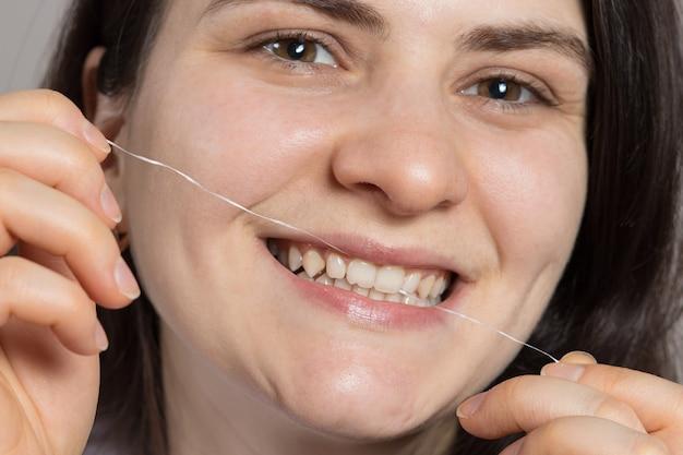 Uma mulher morena escova os dentes com fio dental.