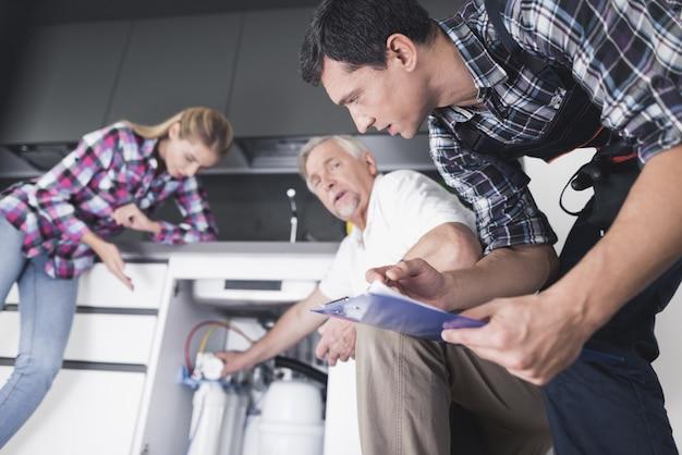 Uma mulher mostra aos encanadores um dissipador de cozinha quebrado.