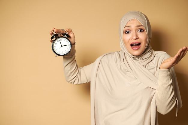 Uma mulher muçulmana atordoada usando um hijab segura um despertador na mão e olha para a frente horrorizada por causa do tempo fugaz