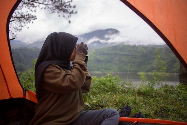 Uma mulher muçulmana fotografando a natureza e as colinas em uma barraca
