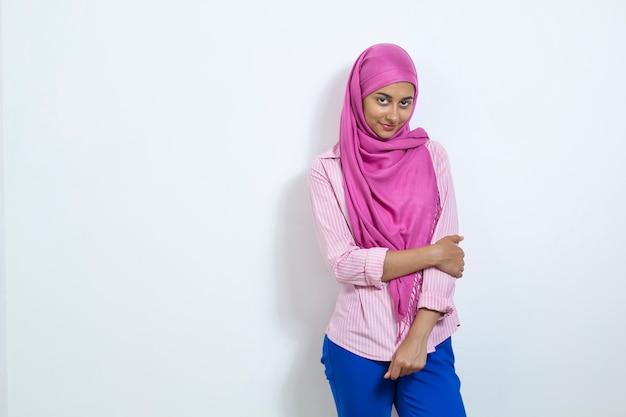 Uma mulher muçulmana vestindo um hijab. menina árabe bonita no fundo branco. copie o espaço.
