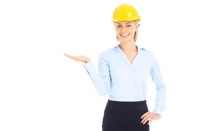 Uma mulher muito elegante com um capacete amarelo apontando sobre um fundo branco