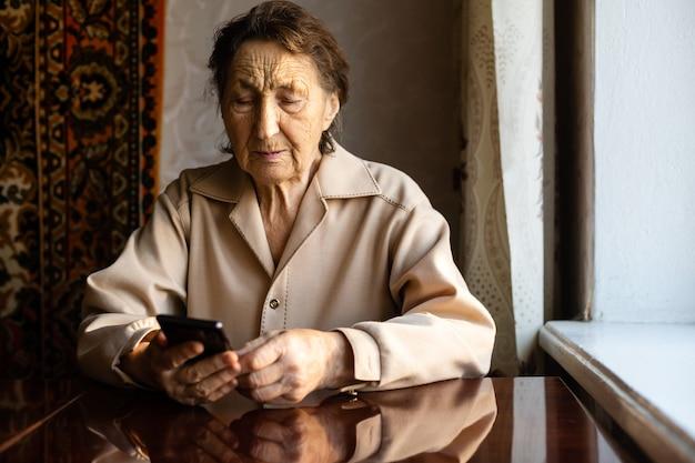 Uma mulher muito velha usa um smartphone em casa.