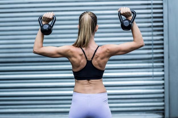 Uma mulher muscular levantando kettlebells