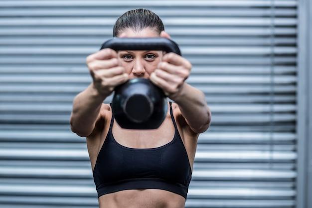 Uma mulher musculosa levantando kettlebells