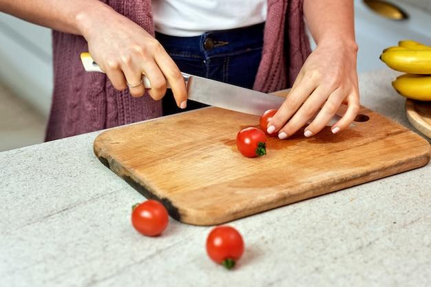 Uma mulher na cozinha cortando tomates para salada