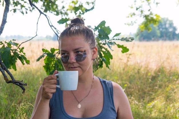 Uma mulher na natureza cuida de seu rosto. bebe chá café na natureza nas férias