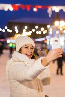 Uma mulher na pista está patinando e tirando selfie no smartphone na véspera de ano novo e na fada do natal