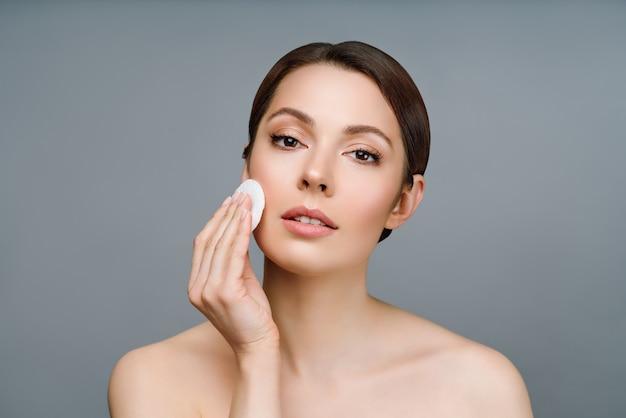 Uma mulher natural com boa pele limpa o rosto com uma almofada de algodão cosmética de beleza