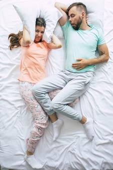 Uma mulher nervosa e estressada está cobrindo os ouvidos com a ajuda de um travesseiro devido ao ronco de seu marido. insônia à noite