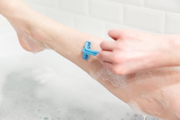 Uma mulher no banheiro raspa as pernas com uma navalha. close de uma mão com uma navalha.