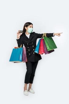 Uma mulher no escuro e usando uma máscara caminha às compras, carrega cartões de crédito e muitas bolsas