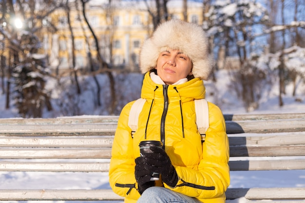 Uma mulher no inverno com roupas quentes em um parque coberto de neve em um dia ensolarado está sentada em um banco e está congelando de frio, é infeliz no inverno, segura o café sozinha