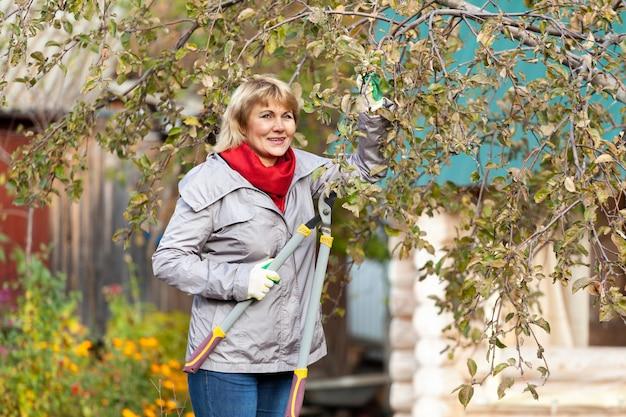Uma mulher no jardim de outono colhe e remove o lixo