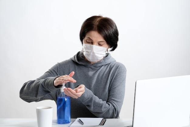 Uma mulher no local de trabalho trata as mãos com um gel antibacteriano