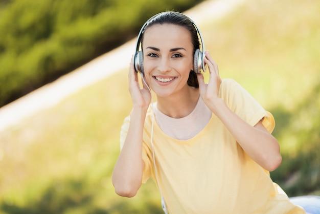 Uma mulher no parque está ouvindo música em fones de ouvido.
