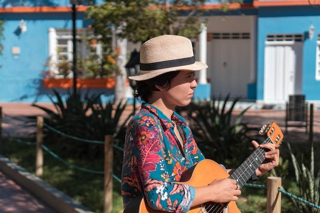 Uma mulher no parque tocando violão