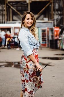Uma mulher nova bonita com cabelo longo com um vidro do café é de sorriso e de riso.