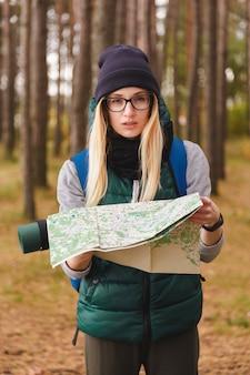 Uma mulher nova bonita com mapa e trouxa do curso em plantações do pinho.