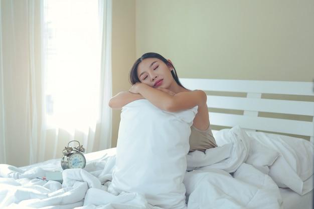 Uma mulher nova bonita está dormindo e um despertador no quarto em casa.