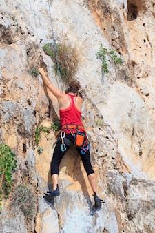 Uma mulher nova com uma corda acoplou nos esportes da escalada na rocha.