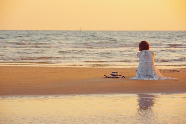 Uma mulher nova está na praia durante um por do sol, férias de verão.