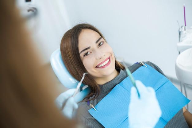 Uma mulher nova está sorrindo com dentes saudáveis brancos ao sentar-se em uma cadeira dental no dentista.