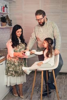 Uma mulher oferece chá à filha e ao marido