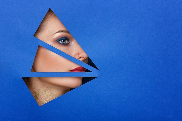 Uma mulher olha no buraco o papel, bela maquiagem.