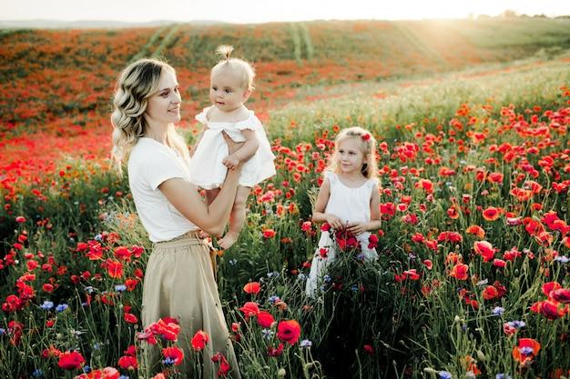 Uma mulher olha para o bebê e a filha mais velha olha para eles