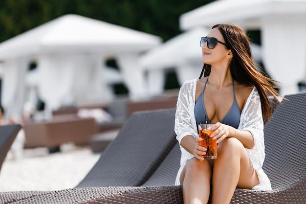 Uma mulher olhando para o mar, enquanto relaxa no solário de luxo.