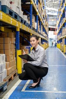 Uma mulher ou mulher de negócios verificando e contando os produtos na prateleira do grande depósito e depósito